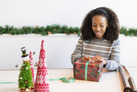 Woman wrapping Christmas present while sitting at table