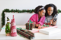 Mother and daughter using mobile phone while sitting with gifts at table