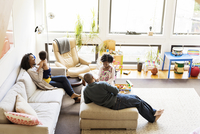 High angle view of family relaxing on sofa