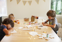 Siblings making craft decorations while sitting at table