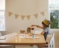 Boy in crown making craft while sitting at table