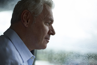 Smiling man looking through wet window while standing at home