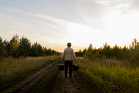 Rear view of man holding buckets while standing on dirt road at field against sky