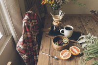 High angle view of fruits with coffee and potted plant on wooden table