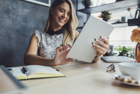 Close-up of happy businesswoman using tablet computer while sitting at table in home office