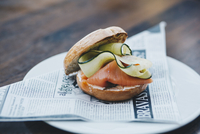 Close-up of salmon burger on newspaper in plate