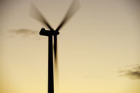 Low angle view of silhouette windmill spinning against sky during sunset