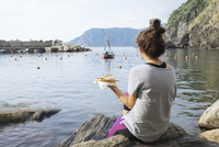 Rear view of woman eating pizza while sitting on rock by sea 11100051931| 写真素材・ストックフォト・画像・イラスト素材|アマナイメージズ