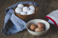 Close-up of eggs in bowls with napkin on wooden table