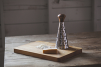 Cheese with grater on cutting board over wooden table