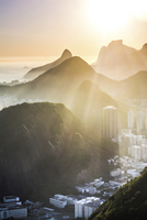 View of sunlight falling on mountains by residential buildings in morning