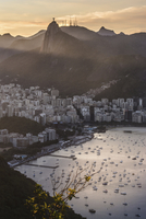 Aerial view of harbor by residential district against mountains at sunset