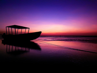 Silhouette boat moored on shore at beach against dramatic sky