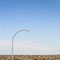 Street light amidst houses against blue sky in town