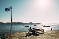 Woman relaxing on bench at pier during sunset 11100052237| 写真素材・ストックフォト・画像・イラスト素材|アマナイメージズ