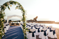 Chairs arranged by sea for wedding ceremony