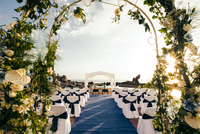 Chairs arranged for ceremony seen through wedding arch