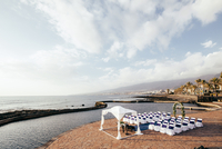 High angle view of chairs arranged by sea for wedding ceremony