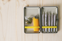 Overhead view of marijuana joints with cigarette lighter in container on table 11100052520| 写真素材・ストックフォト・画像・イラスト素材|アマナイメージズ