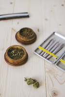 High angle view of marijuana joints with crusher on table