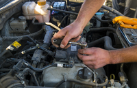 Cropped image of hands repairing vehicle engine