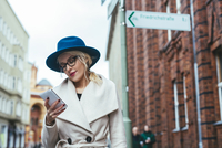 Low angle view of woman using mobile phone while standing on city street 11100052575| 写真素材・ストックフォト・画像・イラスト素材|アマナイメージズ
