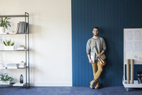 Portrait of man standing against wall in classroom 11100052670  写真素材・ストックフォト・画像・イラスト素材 アマナイメージズ