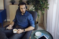 Man holding coffee cup and mobile phone listening music while sitting on chair at home