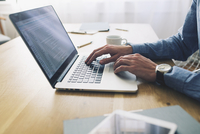 Midsection of businessman using laptop computer at desk in office