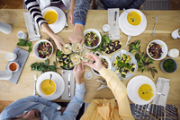 Overhead view of friends toasting champagne flutes while sitting at dinning table in lunch party