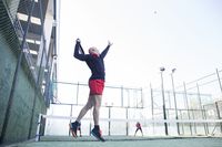 Side view of man playing tennis with friends in court against clear sky