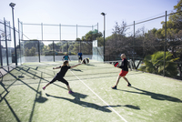 Athletes practicing tennis in court against sky