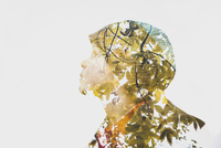 Double exposure of boy and trees against sky