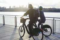 Friends riding bicycle on promenade by river