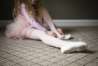 Girl wearing shoe while sitting on carpet at home 11100053169| 写真素材・ストックフォト・画像・イラスト素材|アマナイメージズ