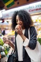 Woman examining tomato at market stall 11100053242| 写真素材・ストックフォト・画像・イラスト素材|アマナイメージズ