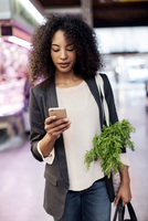 Woman using mobile phone while walking in market 11100053243| 写真素材・ストックフォト・画像・イラスト素材|アマナイメージズ