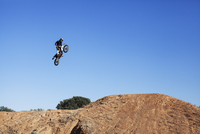 Low angle view of biker performing stunt against clear blue sky