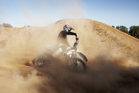 Man riding dirt bike on sand against sky