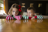 Siblings leaning on table at home