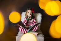 Portrait of cute girl with finger on lips and book sitting on chair at home 11100053380| 写真素材・ストックフォト・画像・イラスト素材|アマナイメージズ