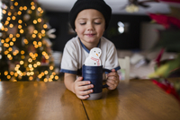 Cute boy holding cup with marshmallow snowman at table in home 11100053384| 写真素材・ストックフォト・画像・イラスト素材|アマナイメージズ