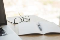 Close-up of diary with pen and eyeglasses on table
