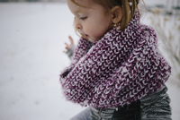 Side view of cute girl in scarf on snow covered field