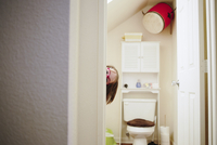 Girl peeking through doorway at home