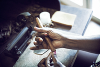 Cropped image of woman making cigar in factory