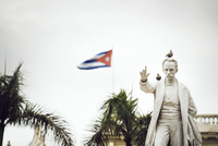 Birds perching on Jose Marti Statue against Cuban flag