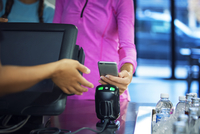 Woman paying bill through smart phone while standing at counter in restaurant