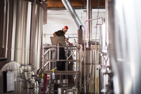 Brewer working while standing by storage tanks at brewery 11100054218| 写真素材・ストックフォト・画像・イラスト素材|アマナイメージズ