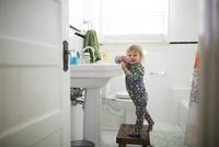 Portrait of cute baby girl brushing teeth while standing on stool in bathroom